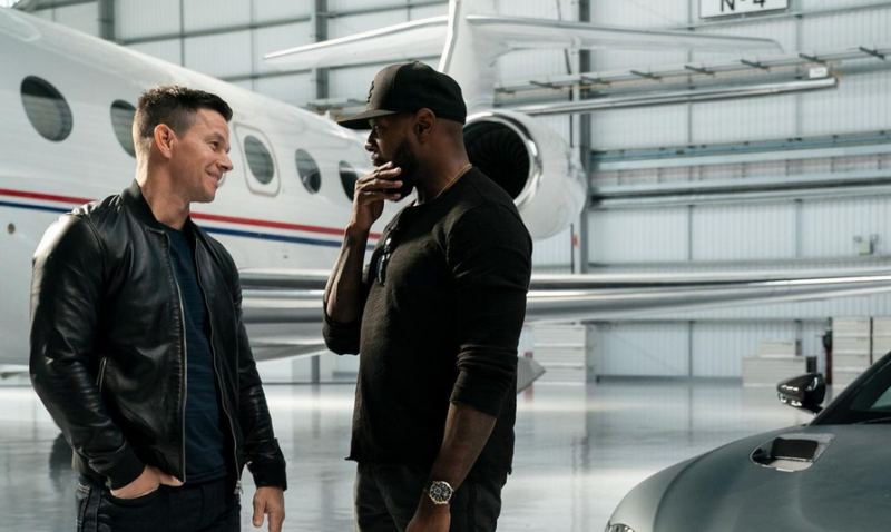 Two cool bros chat in a hangar in front of private jet.