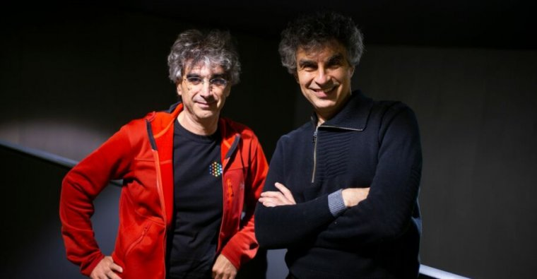 Two casually dressed men with tousled, salt-and-pepper hair pose for a photo.